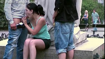 Cute teen girl fucked by 2 guys in PUBLIC in center of the city by famous statue