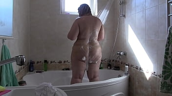 A mature bbw with a juicy PAWG and hairy pussy washes in a bath with soapy foam under the shower Fetish with peeping for porn milf in everyday life at home